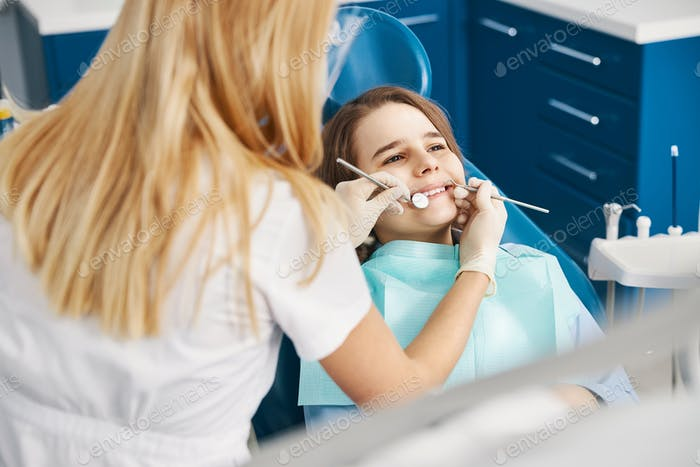 Dental professional conducting dental inspection with probe and mirror