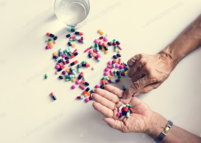 Closeup of hands taking pills health treatment isolated