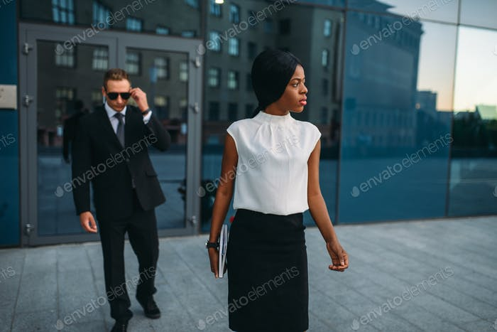 Business woman, bodyguard in suit on background