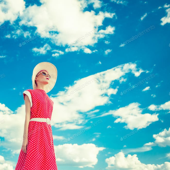 Portrait of retro girl on the blue sky background