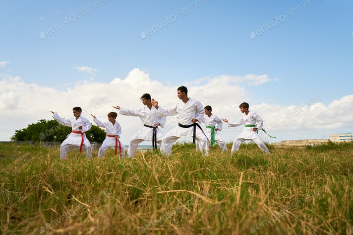 Karate School With Trainers And Boys Warming Up