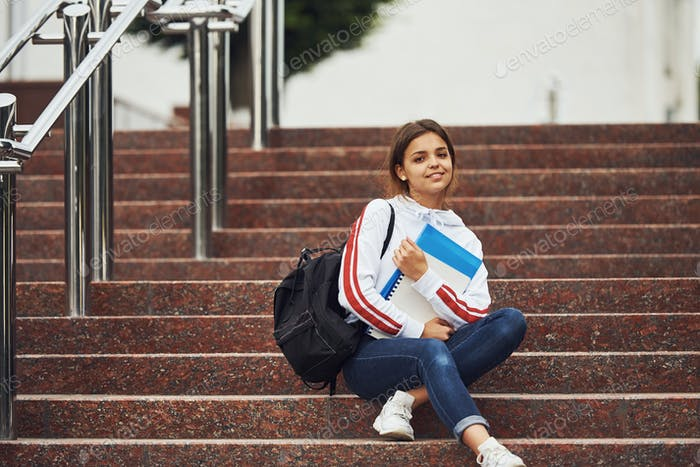Positive female student sitting on stairs outdoors with documents at daytime