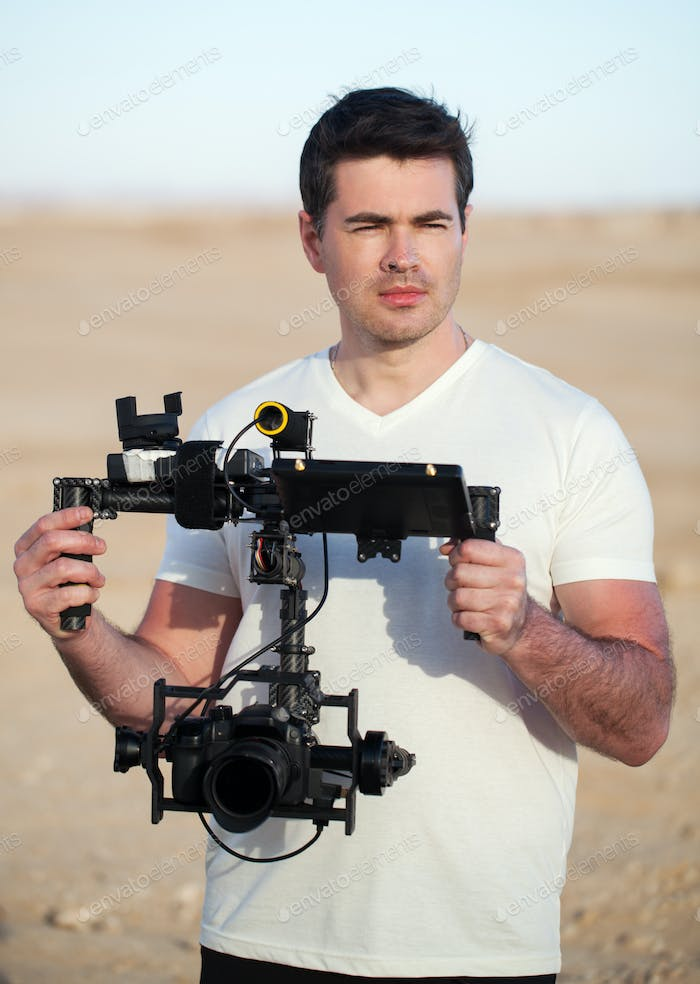 Videographer with steadicam equipment on the beach