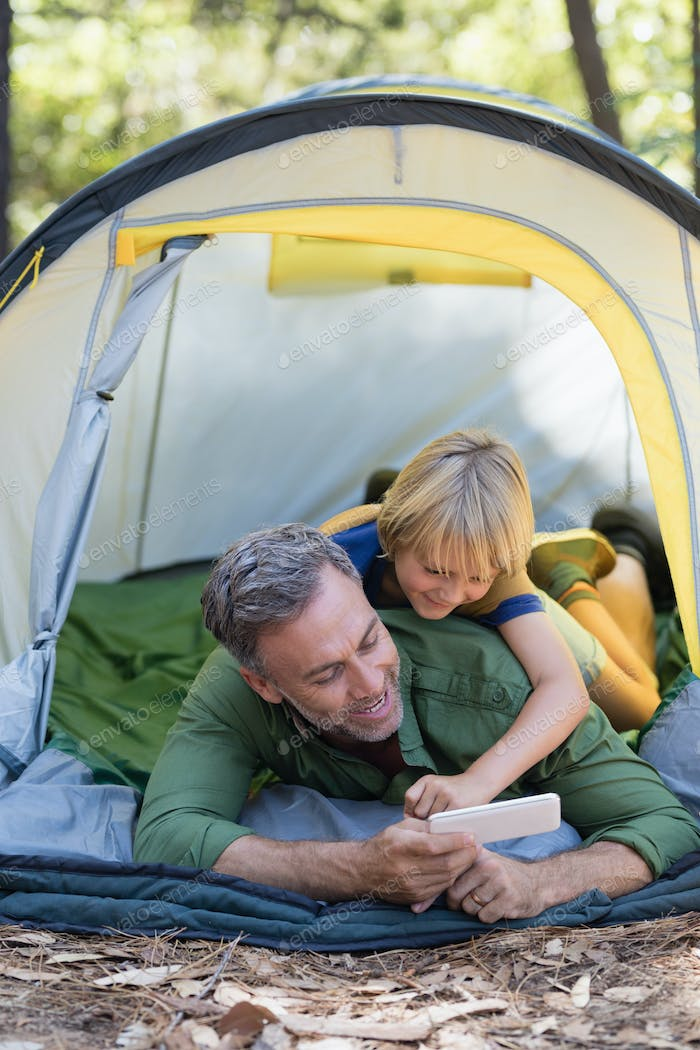 Happy father and son enjoying while using mobile phone at campsite