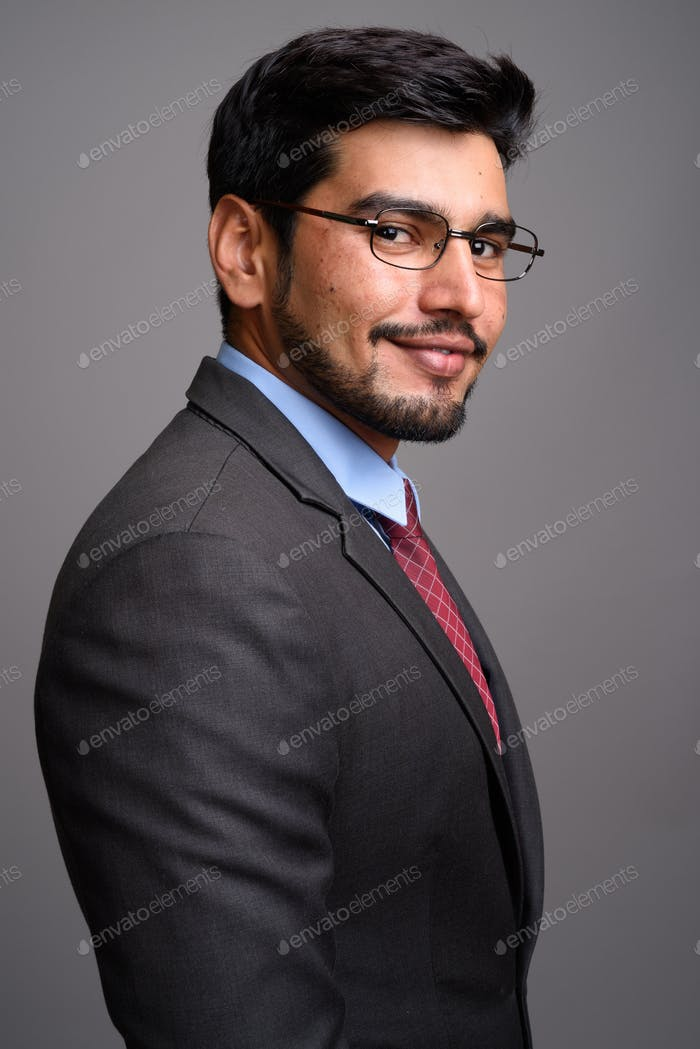 Young handsome bearded Persian businessman wearing eyeglasses