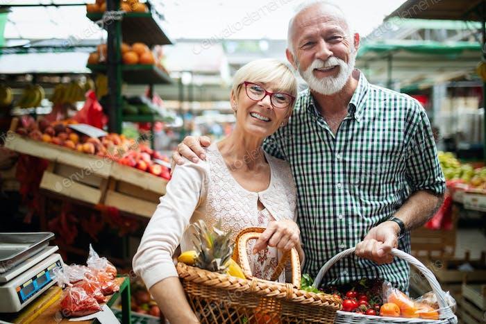Lächelnd Seniorenpaar halten Korb mit Gemüse auf dem Markt