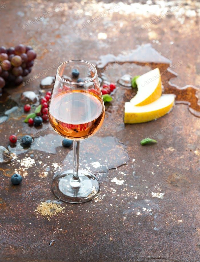 Glas Rosenwein mit Beeren, Melone, Trauben und Eis auf grunge rostigen Metallhintergrund.
