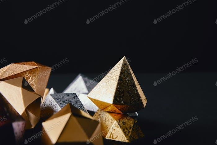 Nahaufnahme von glänzenden facettierten goldenen und silbernen Stücken auf schwarzem Hintergrund