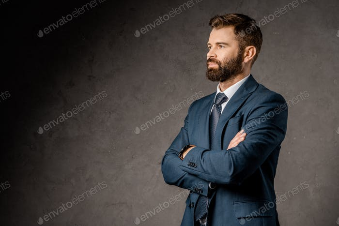 successful bearded businessman standing with crossed arms
