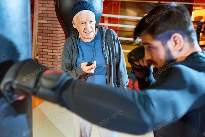 Senior man training young boxer