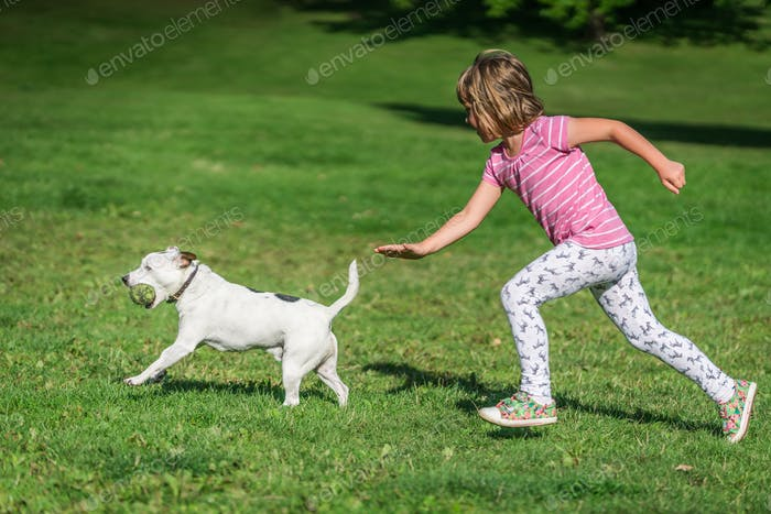 Girl chasing after dog in park