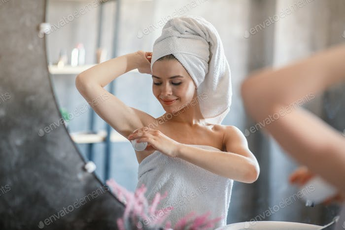 Pretty young woman applying deodorant on armpit in front of mirror at bathroom