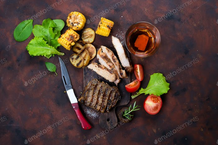 Fresh three types of grilled steak (chicken, pork, beef) on slate plate with herb
