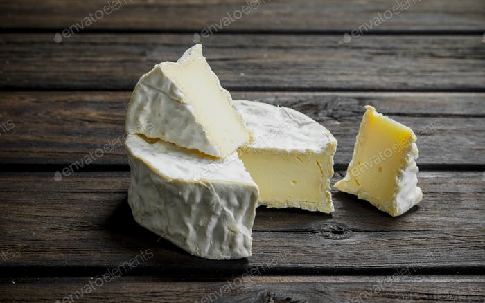 Brie cheese on wooden background.
