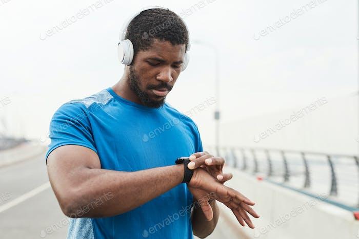 Athlete examining his pulse on fitness bracelet