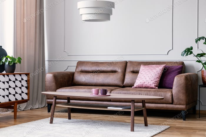 Pillows on leather couch in retro living room interior with lamp Foto von  bialasiewicz auf Envato Elements