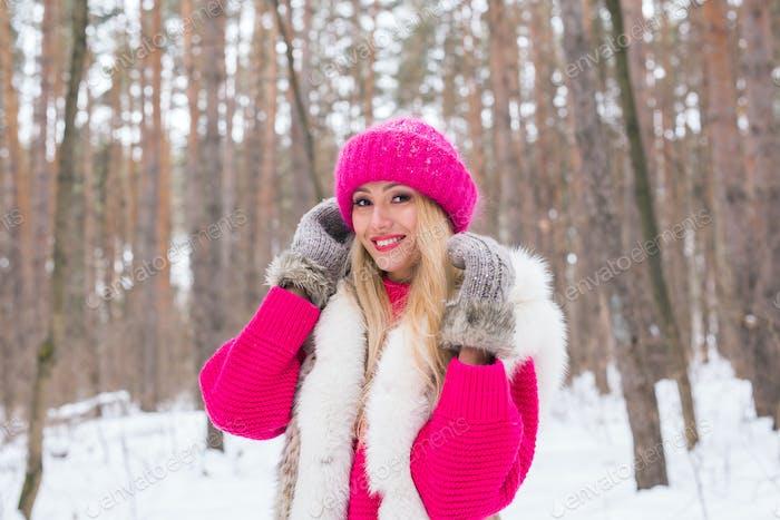 Schönheit, Natur und Menschen Konzept - schöne blonde Frau zu Fuß in rosa Hut und Pullover im Winter