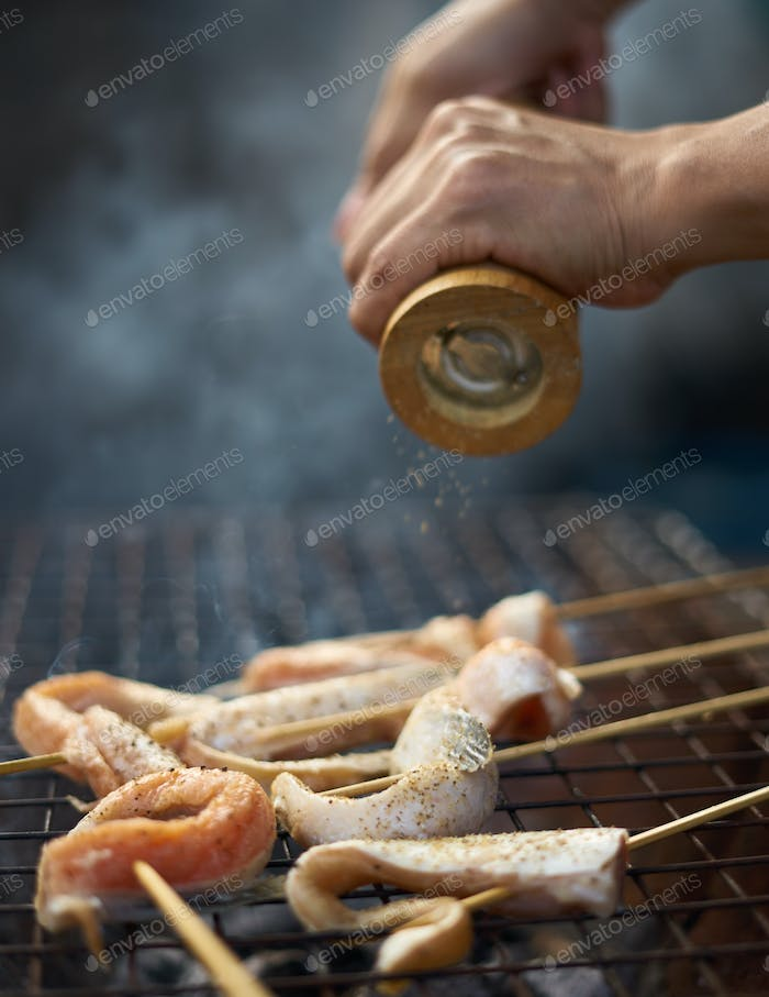 grinding the pepper on meat in grill