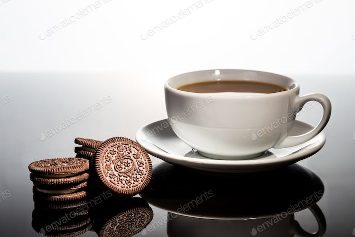 Creme-filled sandwich cookie and milk coffee on dark reflective background