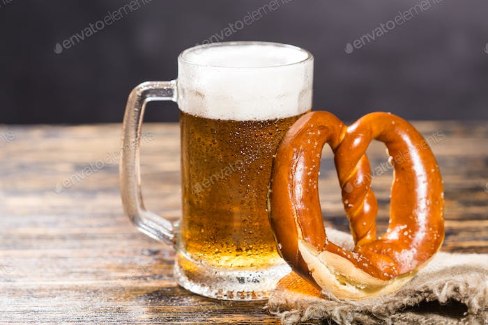 Glass of cold pale beer with a pretzel on a rustic wooden table