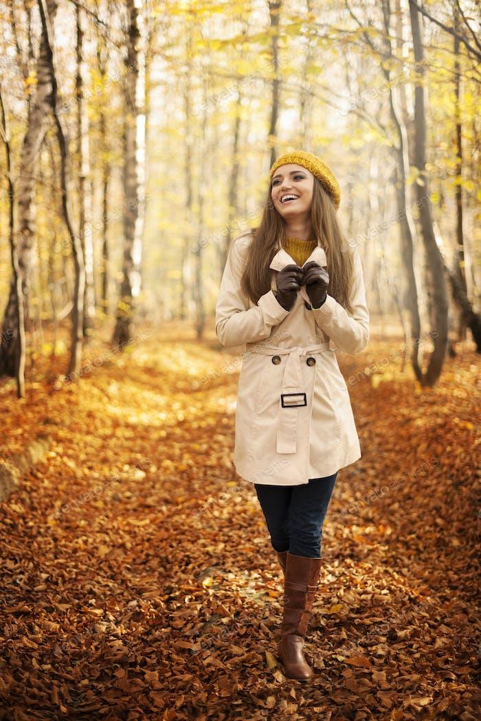 Lächelnde Frau zu Fuß im Park in der Herbstsaison