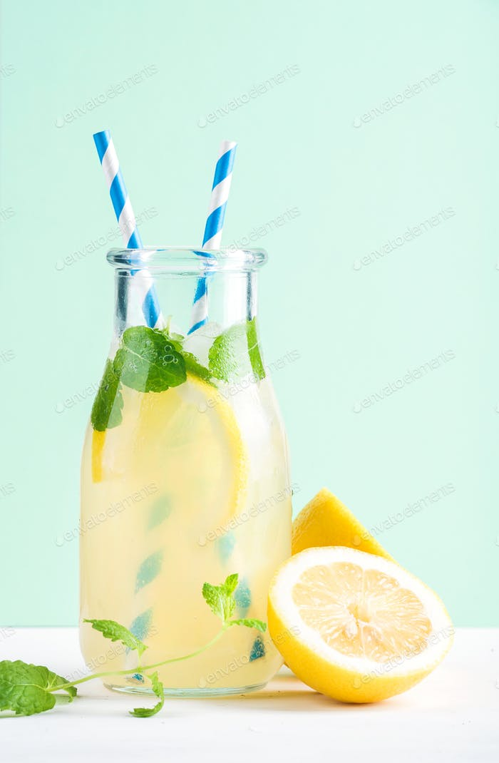 Bottle of homemade lemonade with mint, ice, lemons, paper straws and pastel blue background