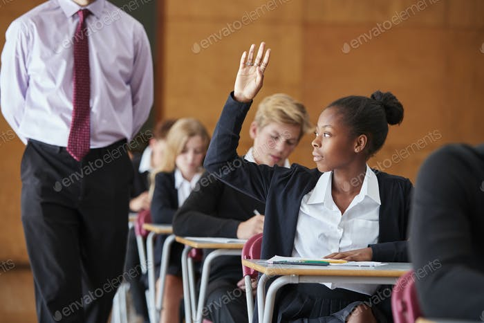 Teenage Student Sitting Examination Asking Teacher Question