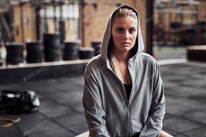 Fit and focused young woman sitting alone in a gym
