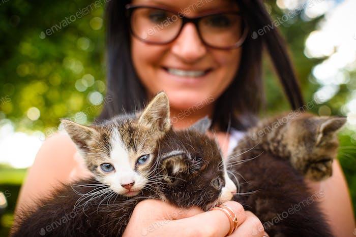 Junge Frau hält entzückende Kätzchen in den Armen