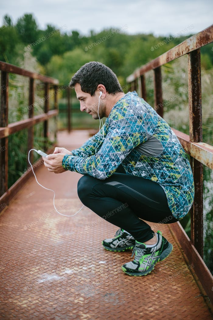 Runner on rusty bridge with smartphone against green nature