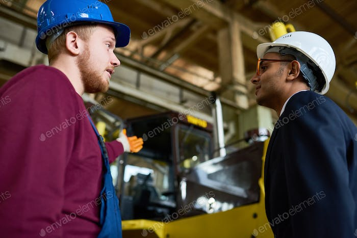 Engineers Discussing Heavy Machinery at Plant