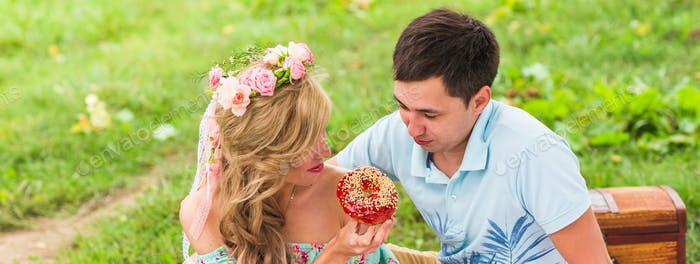 Young funny love couple on date in nature picnic with donuts