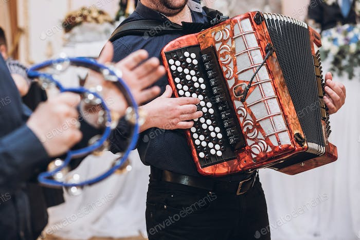 musicians playing on accordion and tambourie