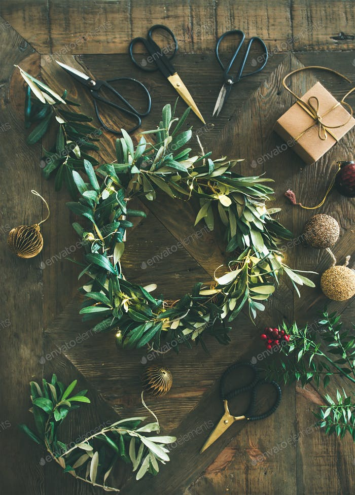 Flat-lay of Christmas decoration toys and wreath over wooden background