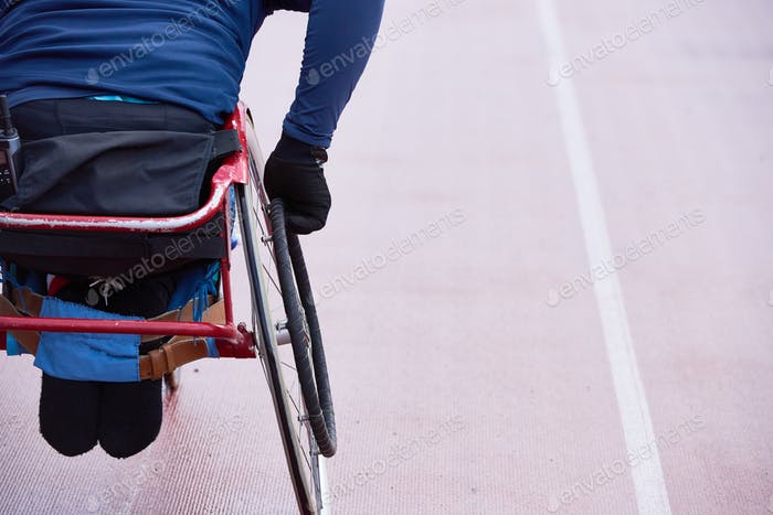 Rear view of physically impaired athlete moving in racing wheelchair on track
