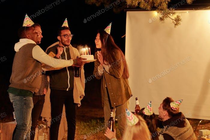 Junge asiatische Frau und gemischte Rasse Mann mit Bier blasen Kerzen auf Geburtstagskuchen