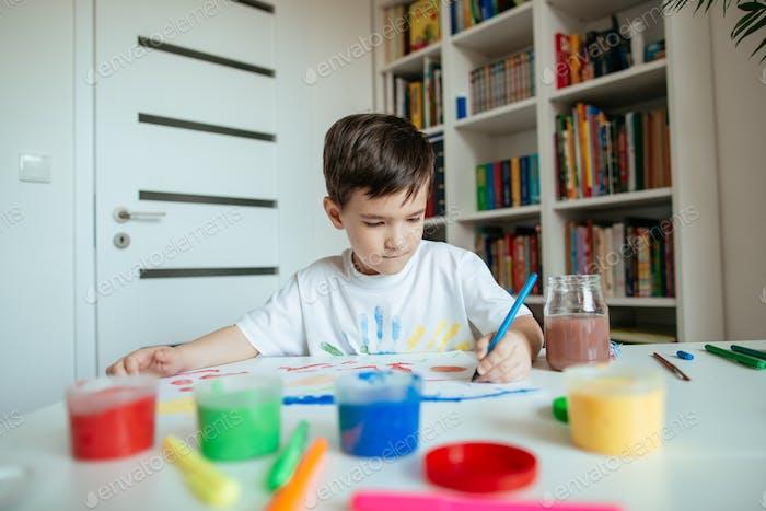 Preschooler boy draws with left hand.