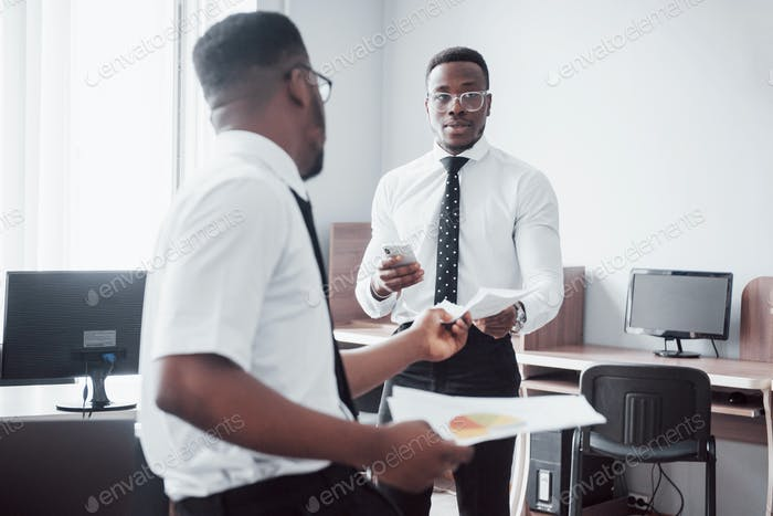 Discussing a project. Two black business people in formalwear discussing something while one of them