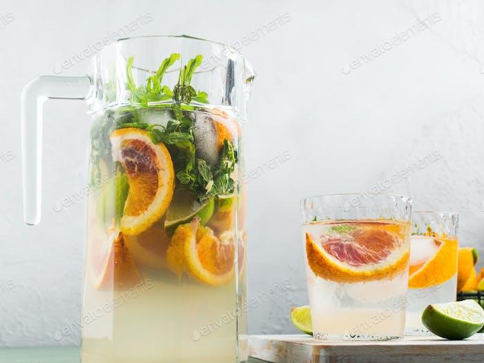 Frischer Sommer Zitrusgetränk im Glas auf grau