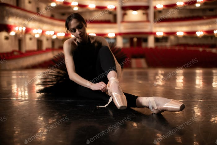 Ballerina sitting on the floor of the beautiful theatre, putting