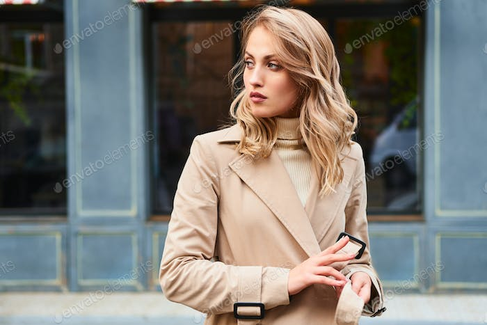 Beautiful blond girl in stylish trench coat thoughtfully looking aside on city street