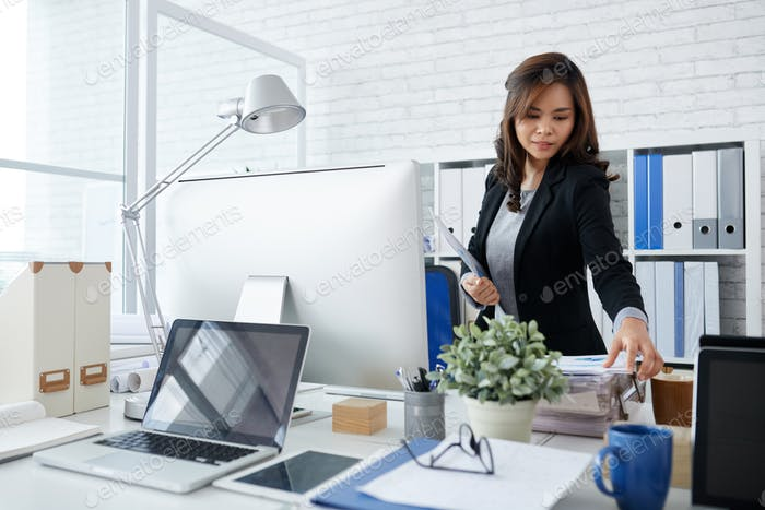 Businesswoman Taking Document from Stack