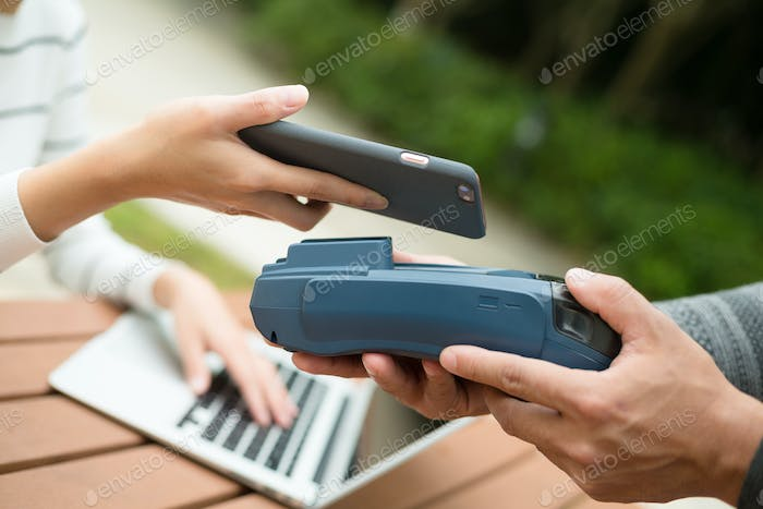 Woman pay by cellphone on pos machine
