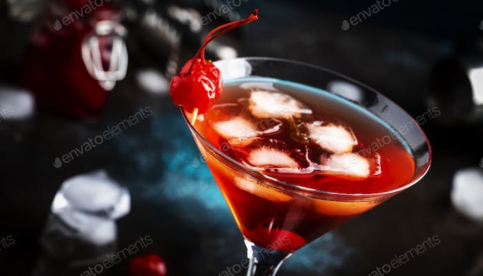Manhattan alcoholic cocktail with bourbon, red vemuth, bitter, ice and cocktail cherry