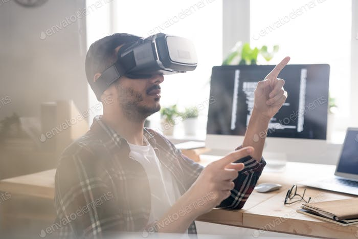 Contemporary software developer in vr headset pointing at virtual display
