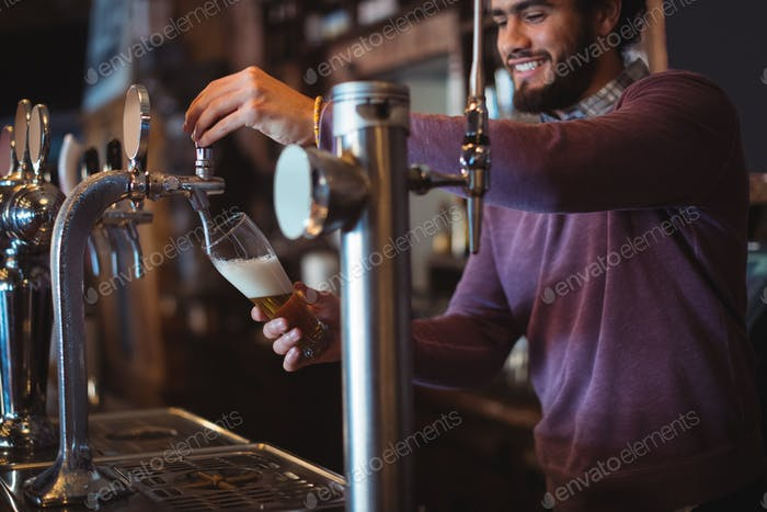 Bar tender filling beer from bar pump