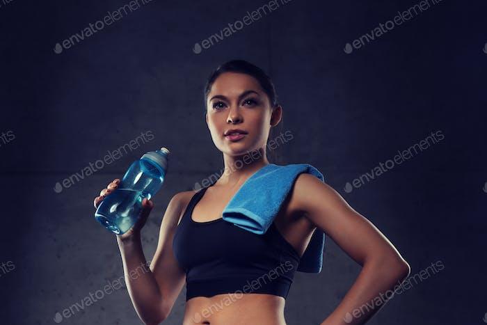 Frau mit Handtuch Trinkwasser aus der Flasche im Fitnessstudio