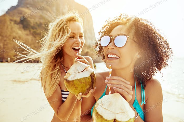 Laughing friends in bikinis drinking from coconuts on a beach