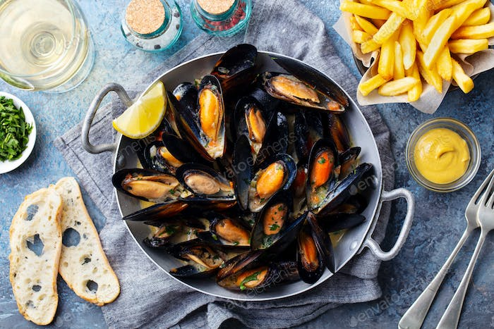 Mussels with French Fries and White Wine in Cooking Pan. Grey Background. Close up. Top view.