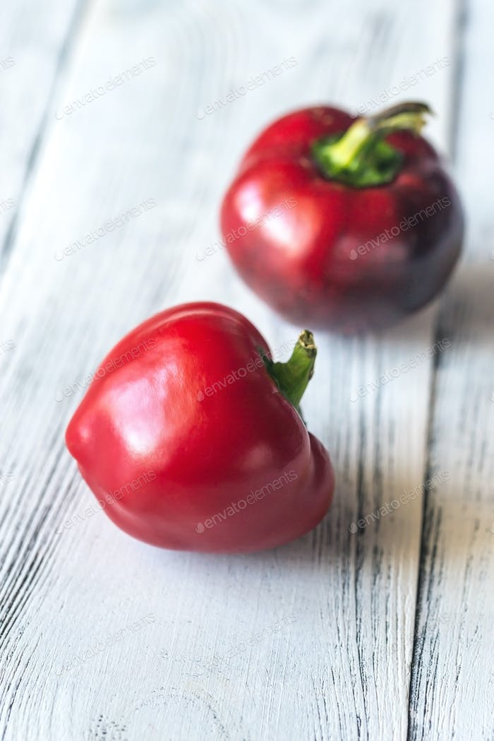 Fresh red bell peppers on the wooden table